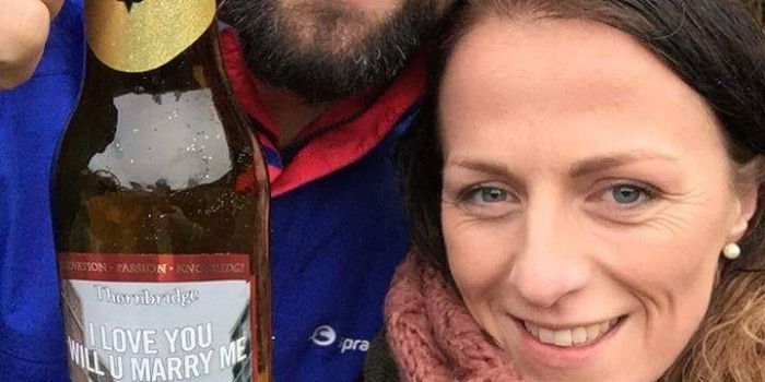 Sinead and Ian with bottle of I Love You Will U Marry Me